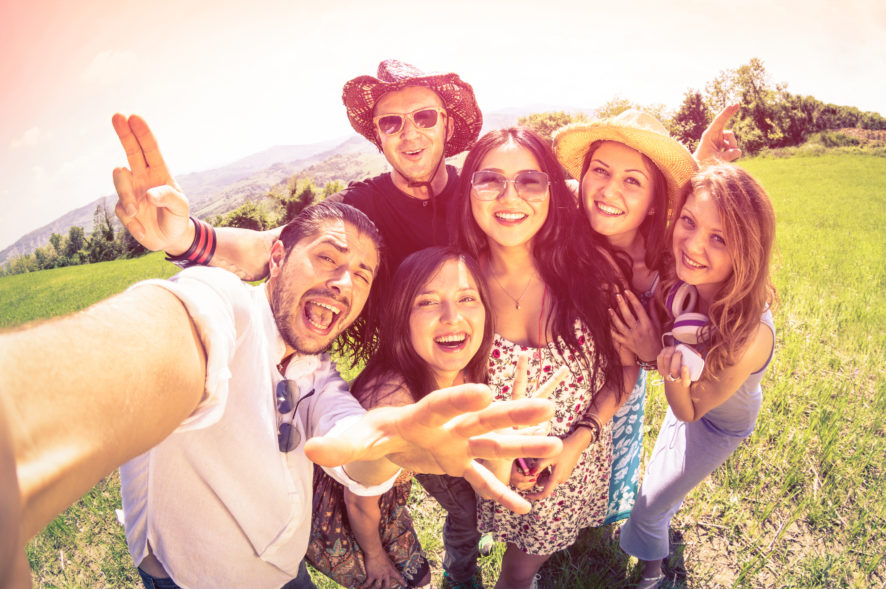 Best friends taking selfie at countryside picnic - Happy friendship concept and fun with young people and new technology trends - Vintage filter look with marsala color tones - Fisheye lens distorsion